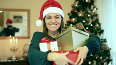 Portrait of happy woman in santa hat holding gift boxes Stock Footage