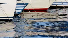 Yachts and prows reflecting on water Stock Footage
