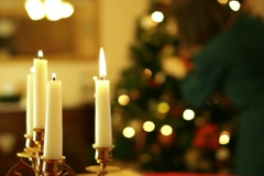 Christmas candles, woman decorating christmas tree in background Stock Footage