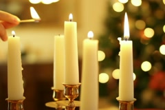 Female hand lighting a candle, christmas tree in background Stock Footage
