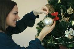 Woman decorating Christmas tree, close up - stock footage