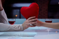 Woman giving red plush heart to man on a date in bar NTSC Stock Footage