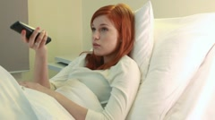 Young red-haired woman watching tv in hospital - stock footage