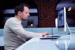 Young man surfing the net on computer in modern interior NTSC - stock footage