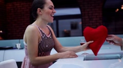 Woman gets red plush heart from man on a date in bar HD Stock Footage