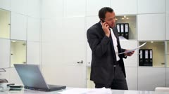 Businessman with documents talking on cellphone in modern office HD - stock footage