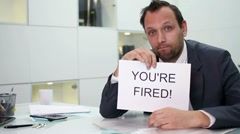 Businessman in office gets paper sheet with YOU`RE FIRED text HD Stock Footage