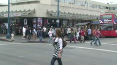 Pedestrians walk across street SF Fishermans Wharf Stock Footage