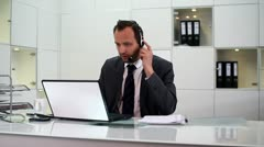 Young helpdesk consultant talking on headset in modern office HD - stock footage