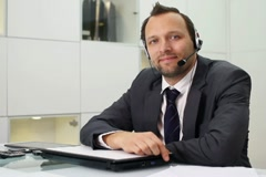 Young helpdesk consultant with headset smiling to camera NTSC Stock Footage