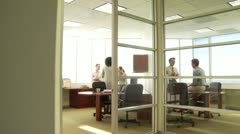 Young business collegues discussing work in two separate offices - stock footage