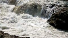 Man Pole fishing on wide waterfall Stock Footage