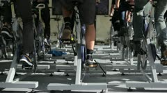 People train out on the stationary bikes at the gym Stock Footage
