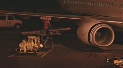 Jetway Worker Refueling Jet at Night 1 Stock Footage