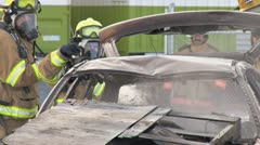 Firefighters Dousing Burnt Wreckage of Car Stock Footage