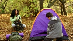 Hiking young couple camping in autumn forest Stock Footage