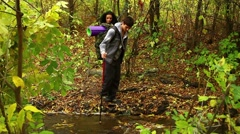 Young couple of hikers crossing a stream Stock Footage