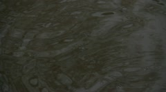 Rain drops circle waves in the puddle surface close Stock Footage