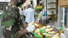 Caribbean man peels an orange with a knife outside a market stall Stock Footage