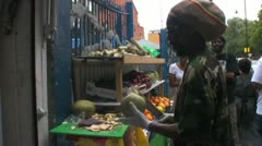 Caribbean man prepares a coconut at a market stall - stock footage
