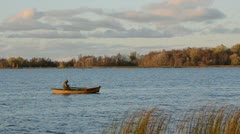 Autumn lake and lonely boat with fisherman Stock Footage