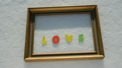 Golden frame on winter snow and word love Stock Footage