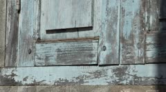 French Colonial: Quick pan left along wall from wooden shutter to broken brick Stock Footage