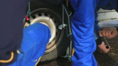 Men Putting Snow Chains Onto Tyre Of Car Stock Footage