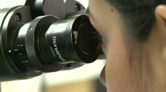 Young female scientist uses microscope - stock footage