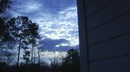 Multilayer clouds time lapse from side of a house Stock Footage
