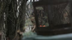 Homeless man warming up in front of a fire - stock footage