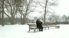 Lonely Senior Woman In Snowy Park Stock Footage