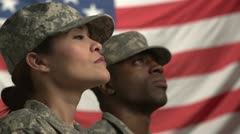 Two U.S. soldiers looking up in front of the flag Stock Footage