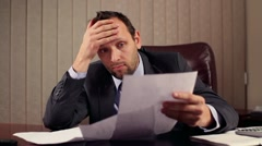 Young boss overwhelmed by too much paperwork in office, steadicam shot HD Stock Footage