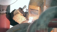 Welder in protective helmet works at factory Stock Footage