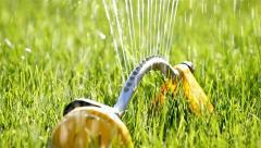 Sprinklers. Sprinkler spraying water on back yard green grass Stock Footage