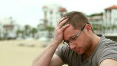 Sad pensive man sitting by the beach, outdoors Stock Footage