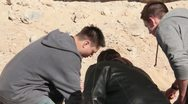 Teenagers looking at something in the dirt Stock Footage