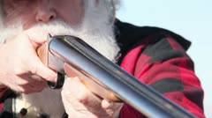 Old man with white beard shooting a shotgun Stock Footage