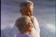 A senior couple walks along the beach at sunset Stock Footage