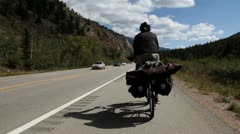 Touring bicyclists ride down highway mountains stock video footage - stock footage
