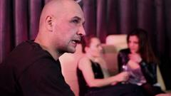 Man drinking in nightclub, women in background, steadicam shot HD Stock Footage