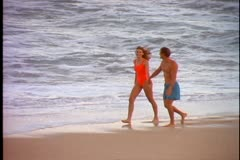A young couple in swimwear walk along the beach Stock Footage