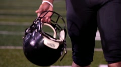 Stock Video Footage of Football player with helmet in hand, walking towards camera.
