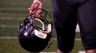 Football player with helmet in hand, walking towards camera. Stock Footage