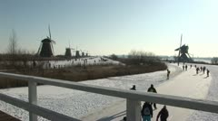 Skaters past the windmills of Kinderdijk, Holland Stock Footage