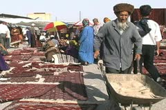 Turkmenistan Tolkuchka market man with wheel barrow Stock Footage