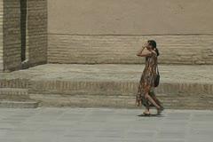 Uzbekistan Khiva girl in colorful dress walking Stock Footage