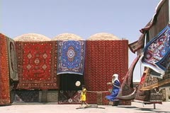 Uzbekistan Bukhara rugs hanging wind blowing Stock Footage