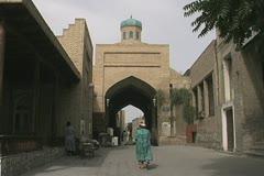 Uzbekistan Bukhara walking toward arch Stock Footage
